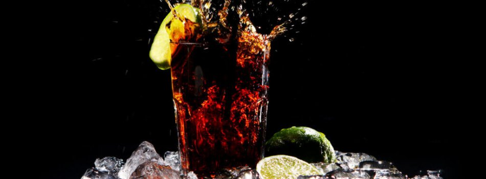 Fresh cola drink with splashes of water and green lime on black background
